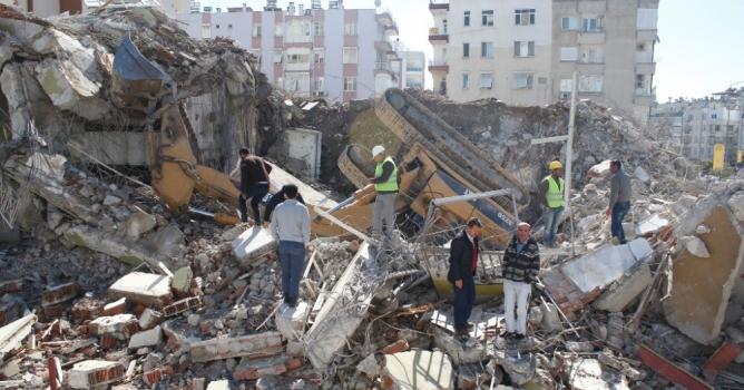 Binada yıkım çalışması yapan iş makinesi devrildi