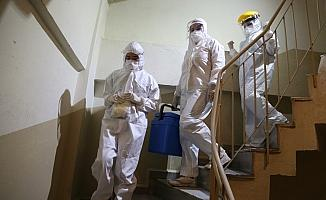 Sıcaklara rağmen koruyucu kıyafet içinde ev ev gezip korona virüsle mücadele ediyorlar
